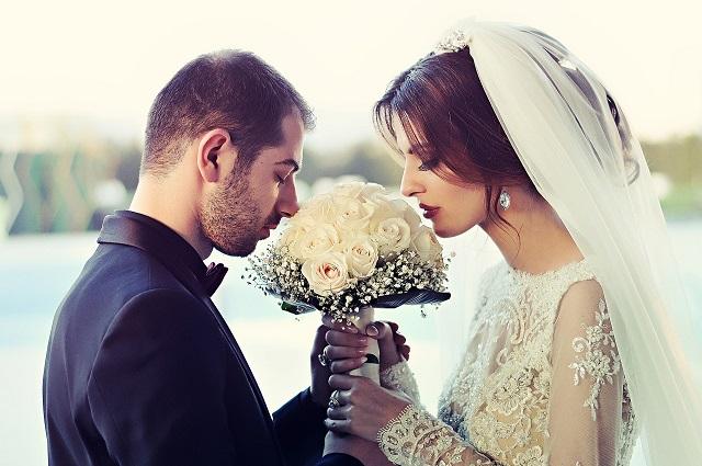 お互いに向き合って一つの花束を持ち結婚を誓う新郎新婦