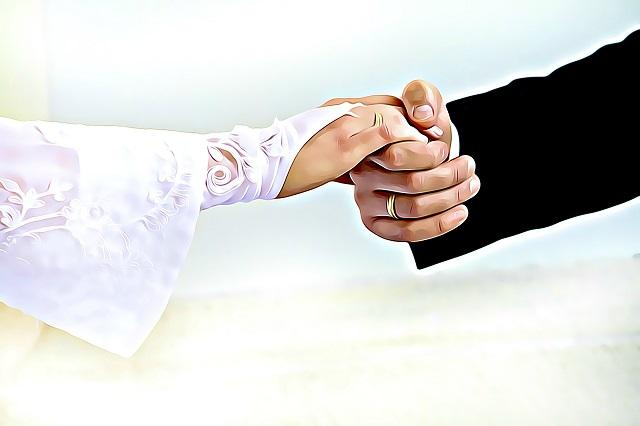 ウェディンググローブをつけた花嫁の手を取る新郎の頼もしい手