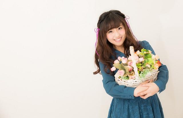 若い女性がかごに入った花束を持って笑顔になっている様子