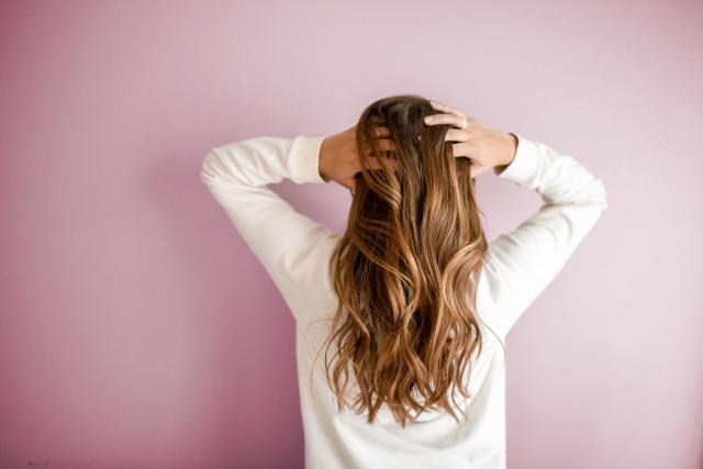 ロングヘアーの女性が髪をかき上げている様子を後ろから撮った写真