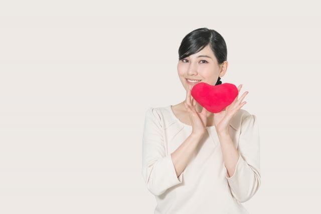 赤いハートのクッションを両手で持ち笑顔の女性