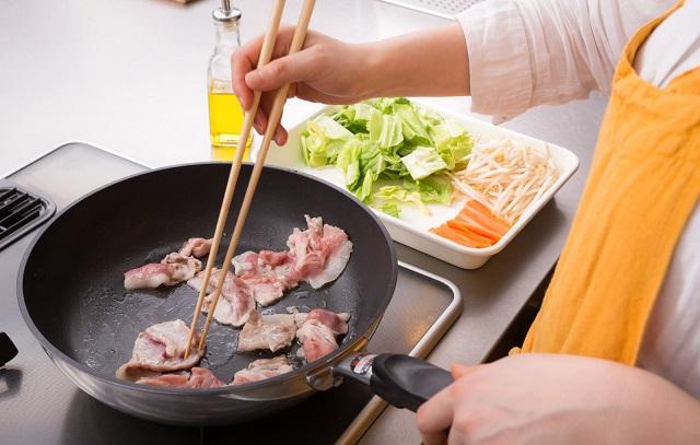 フライパンでお肉を焼くお母さん