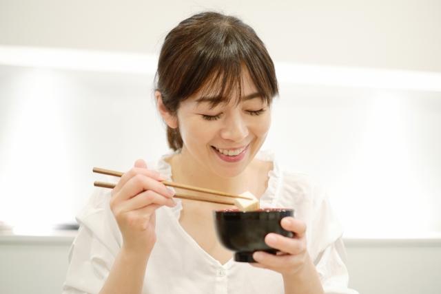 お椀に入った味噌汁から豆腐を箸ですくい今食べようとしている女性