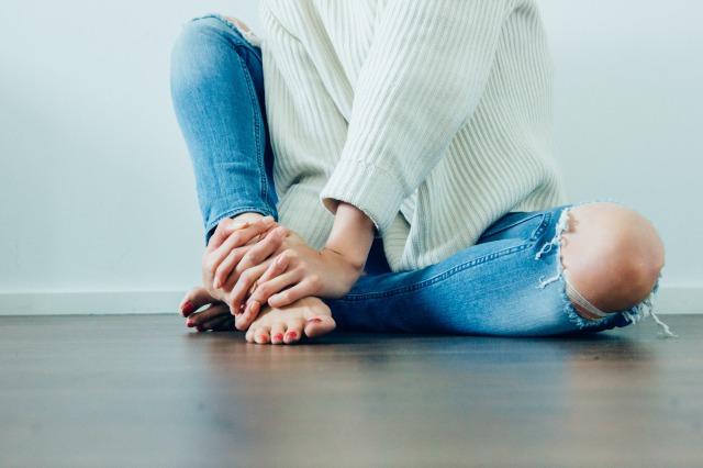 ジーンズをはいた女性が脚を触っている