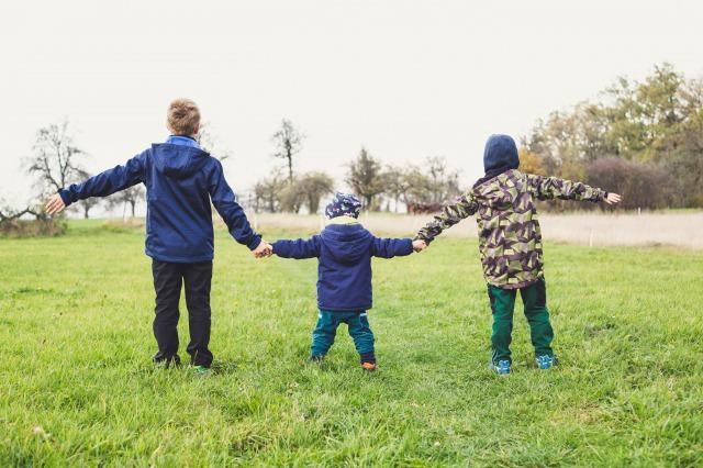 3人の子供が手をつないで立っている