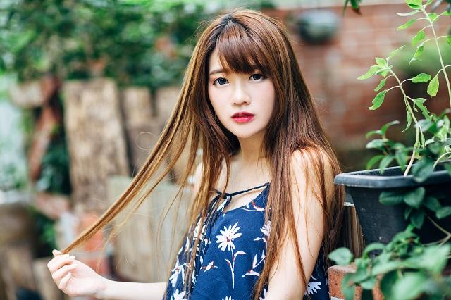 青い服を着た髪が長いアジア系の女性