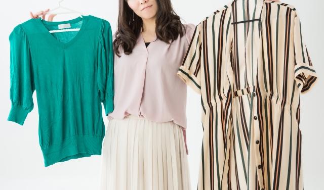 服をどちらがいいか選ぶ女性