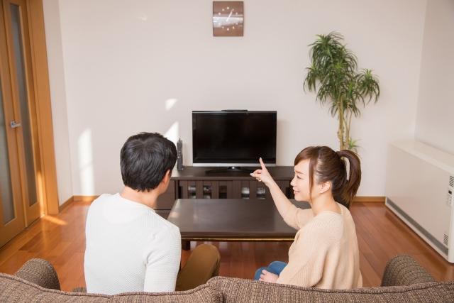 ソファに座りテレビを指さし何か話をしている夫婦