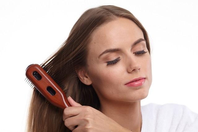 外国人の女性がブラスで髪をとかしている様子