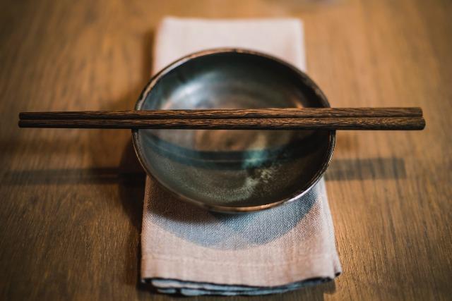 折りたたまれたキッチンマットの上に置かれた陶器の皿と箸