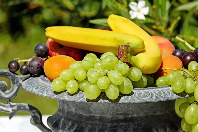 バナナやぶどう柿などのフルーツが皿に置かれている