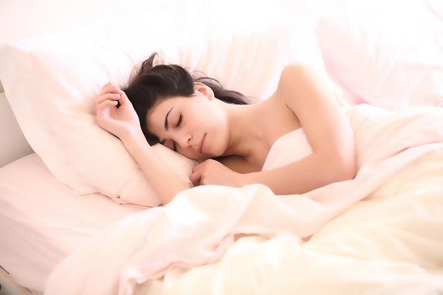 うすいピンクのベッドに寝ている外国人の女性