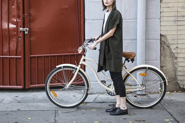 路地で自転車のサドルを持ち立っている若い女性