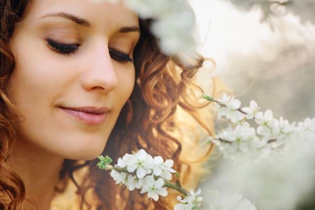 白い花の匂いをかぐ女性