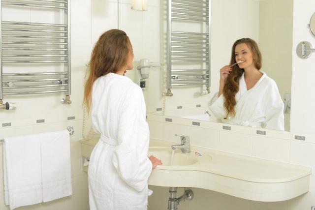 鏡を見て歯磨きをする白いガウンを着た女性