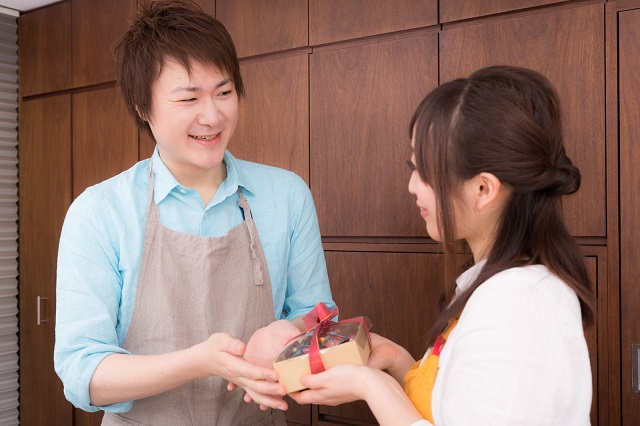 エプロンをつけた女性がエプロンをつけた男性にチョコを渡している