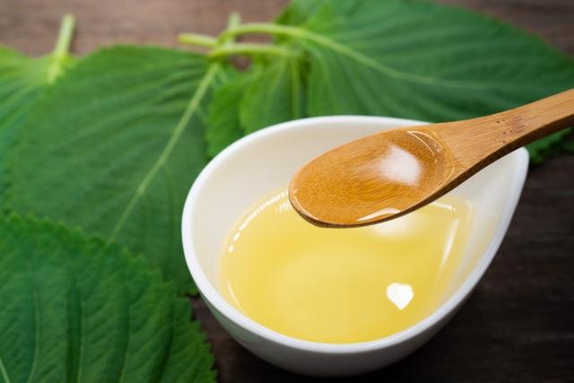 大きな葉っぱの上の白い器に黄色いオイルが入っていて、それを木のスプーンですくっている様子