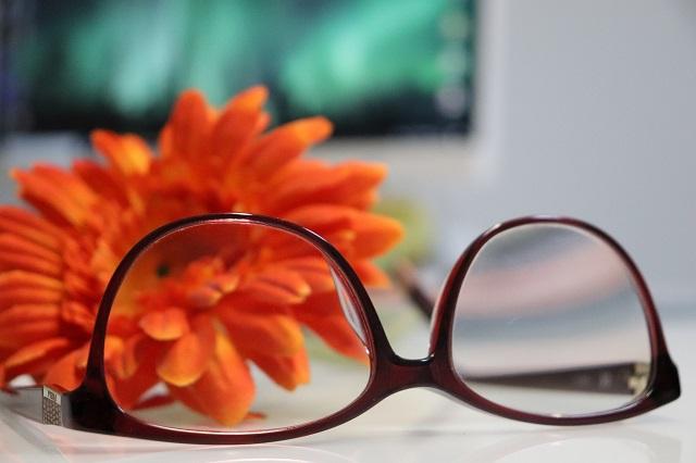 眼鏡とオレンジ色の花