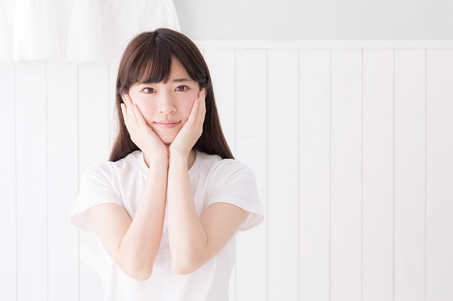 若い白いTシャツを着た女性が両手で両頬を触っている様子