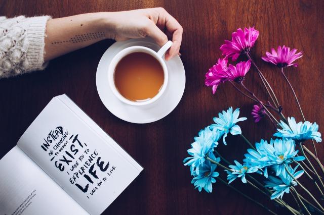 文字が書かれたノートとピンク&水色の花が置かれたテーブルで紅茶のカップの取っ手を握っている女性の手