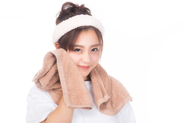 茶色いタオルで顔を拭いている女性