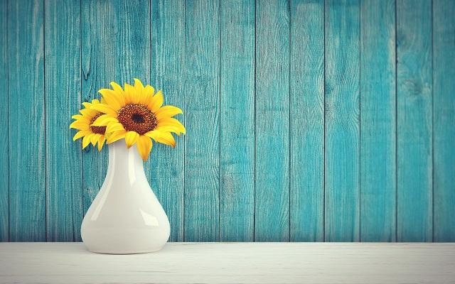 白い花瓶にひまわりの花が2本入っている