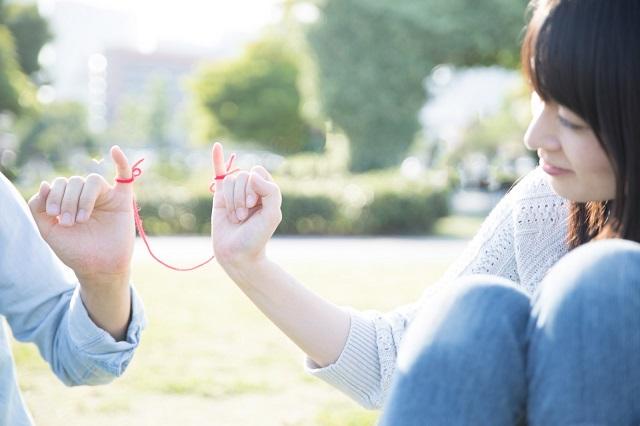 カップルが小指に赤い糸をつけてずっと一緒にいたいことを確認している様子