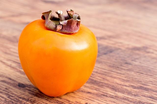 木のテーブルに乗っている一個の柿