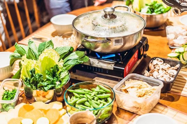 食卓に置かれたきのこや枝豆などの野菜、そしてその真ん中にコンロに火をつけた鍋が置かれている