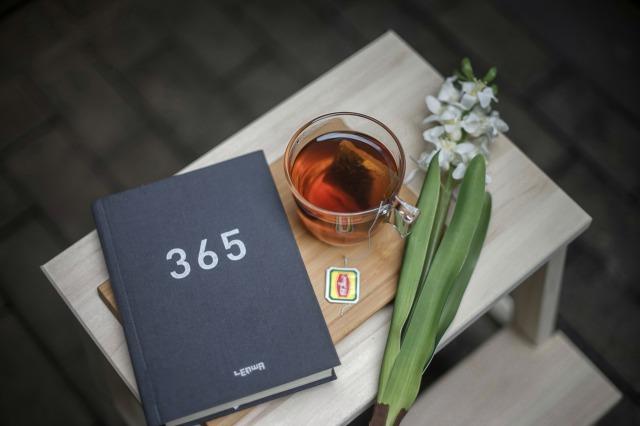 365と書かれたノートと紅茶とすいれんの花が小さなテーブルに乗っている