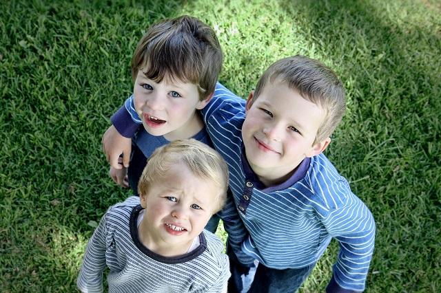 3人の男の子が集まって上を向いている