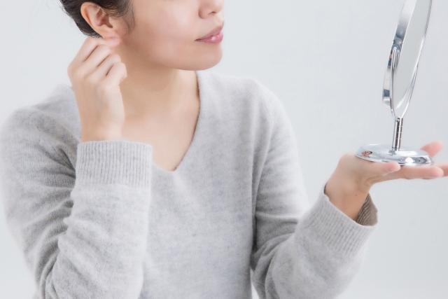 鏡を持ち片方の手で耳たぶを触っている女性
