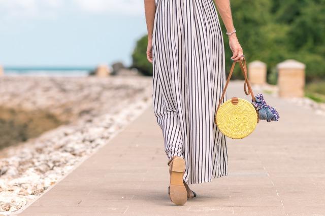 海辺をボーダー柄のワンピースを着て歩いている女性