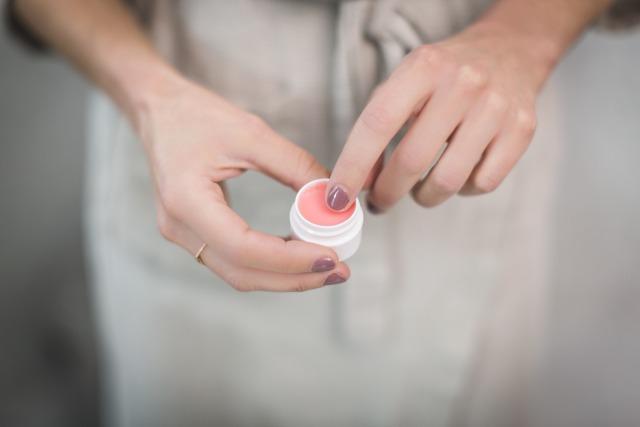 小さなハンドクリームを手に塗ろうとしている女性