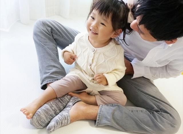 子供をひざに乗せて笑っている夫