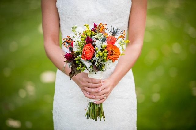 白いドレスを着た女性がオレンジ色や白紫などの様々な色の花束を両手で持っている様子