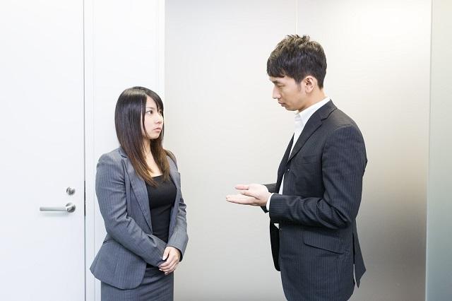 会社の社員である男女が話をしている様子