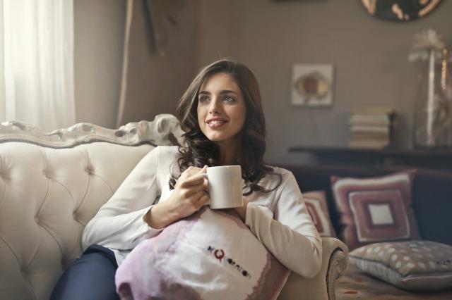白いマグカップを持ってソファに座る女性