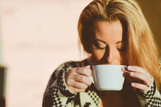 マグカップで何かの飲み物を飲んでいる外国人の女性