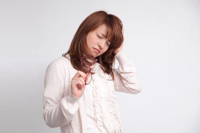 眼鏡を持ち頭をかき眠そうにしている女性