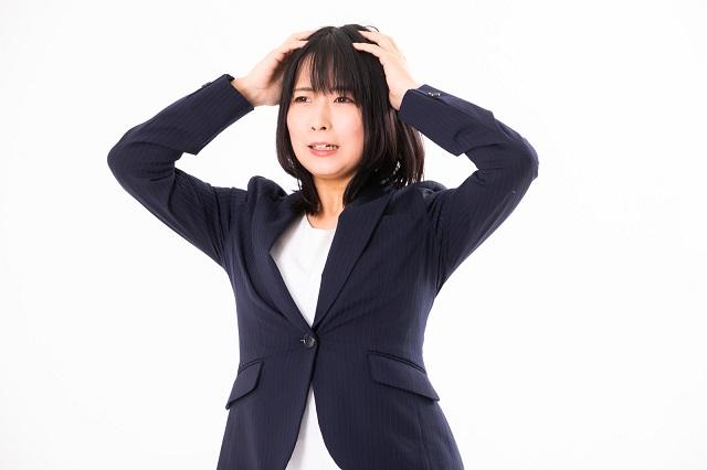 頭に手をあてて不安な顔をしているスーツを着た女性