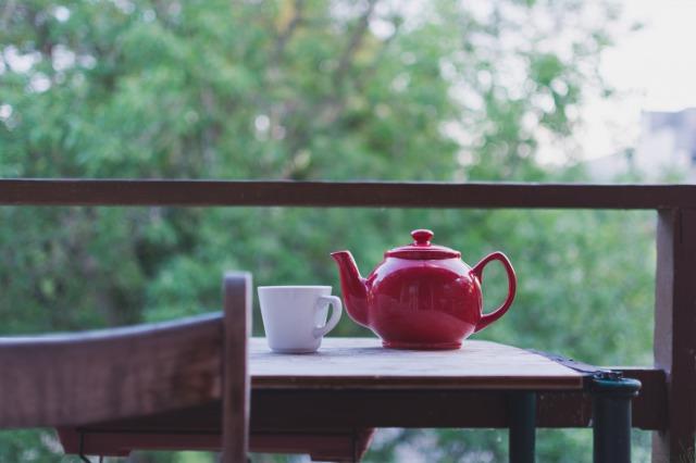 庭のテーブルの上に置かれた赤い急須と白いマグカップ