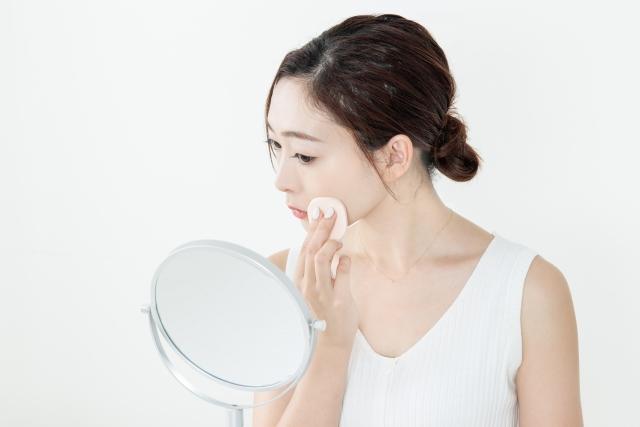 鏡を見ながらフェイスパウダーを塗っている女性