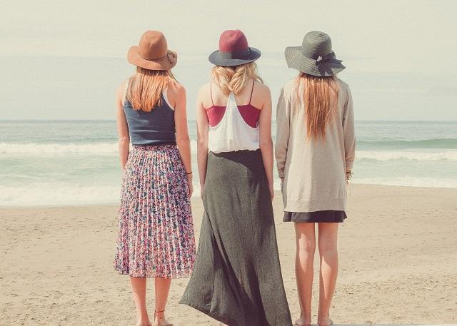 海辺で3人の女性が海の方を見て立っている後ろ姿