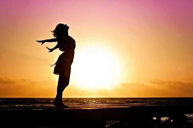 両手を広げて夕日を浴びている女性の影